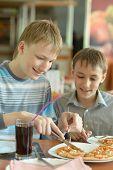 boys eatning pizza in cafe