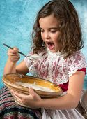 Vintage girl with lace collar and apron eating food she dislikes