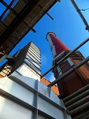 Old, Tall Industrial Chimney Of Brick And Exhaust Ducts