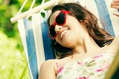 Young woman lying in a hammock in garden with heart shaped sunglasses.
