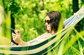 Young woman lying in a hammock in garden with E-Book on tablet computer.