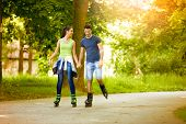 Affectionate couple having leisure recreation with rollerblades at park