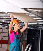 Man in builder uniform installing suspended ceiling