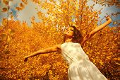 Enjoying the nature. Young woman arms raised enjoying the fresh air in autumn forest.