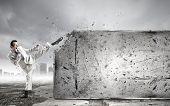 Businessman breaking stone wall with karate kick