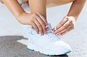 Close up of woman in sport wear tying shoelace