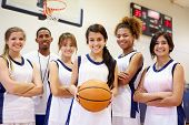 Members Of Female High School Basketball Team With Coach