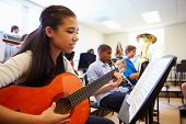 stock photo of pupils  - Female Pupil Playing Guitar In High School Orchestra - JPG