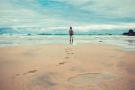 stock photo of footprint  - Footprints left on the beach by a young woman