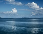 Calm tropical sea and clouds in the sky