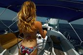 Young lady in bikini steering the yacht