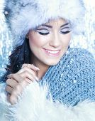 Winter face close up of young attractive  smiling woman covered with snow flakes. Christmas concept.