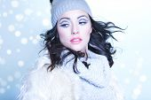 Winter face close up of young attractive woman wearing hat and fur covered with snow flakes. Christmas concept.