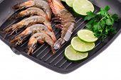Fragment raw shrimps on frying pan.