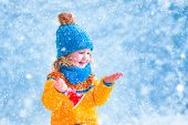 stock photo of new years baby  - Adorable little girl cute toddler in a blue knitted hat and yellow nordic sweater playing with snow catching snowflakes and ringing her Christmas toy bell having fun outdoors in a beautiful winter park - JPG