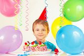 Little blonde boy in festive hat with birthday cake and balloons