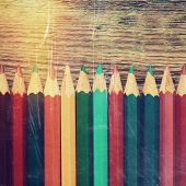 Row Of Colored Drawing Pencils Closeup On Old Desk. Vintage Stylized.