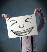 Businessman holding a paper with a drawed smiley face on it in front of his head