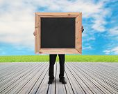 Businessman Holding Black Blank Chalkboard With Natural Sky Meadow