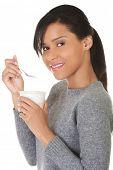 Side view healthy woman eating yoghurt.