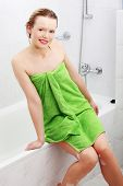 Happy young woman wrapped in towel after bath.