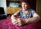 Old woman. Elderly sad female at home