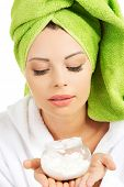 Woman wrapped in towel with cream container.