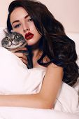 Beautiful Brunette Holding A Cat ,lying On Bed In Bedroom