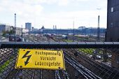 Yellow Sign Showing High Voltage At A Train Station