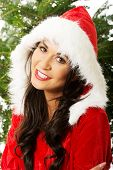 Portrait of santa woman with christmas tree on a background, looking at the camera.
