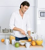 Man in the kitchen cutting oranges for breakfast