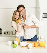 Couple preparing a healthy breakfast with fruit and cereal