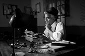 picture of 1950s style  - Professional reporter working late at night at his desk with vintage typewriter 1950s style - JPG