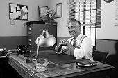 Smiling Vintage Director Sitting At Office Desk