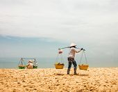 PHU QUOC, VIETNAM - APRIL 18, 2014: Vietnamese womans in traditional headdress, which protects from the sun offers fruits for sale to tourists at Long beach on Phu Quoc island, Vietnam.