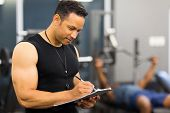 muscular mid age male gym trainer writing on clipboard