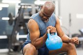 strong young african american man lifting kettle bell in gym