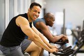 two men doing indoor biking in a fitness club