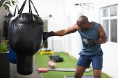 fitness african man training with punch bag in gym