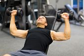 strong middle aged man lifting weights in gym