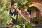 Woman with vintage bike  in Tuscany garden
