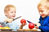 pic of unawares  - Children little boys brothers playing dangerous game with kitchen knife cutting apple making salad at home - JPG
