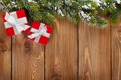 Christmas gift boxes and snow fir tree over wooden background with copy space