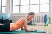 Woman Using Smart Phone While Exercising At Gym