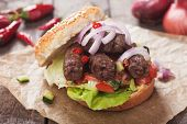 Turkish kebab grilled meat in burger bun with onion and salad