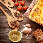 ready lasagna and its ingradient on a wooden table