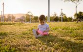 Happy baby girl playing sitting on a grass park
