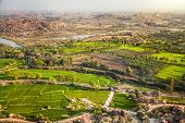 stock photo of karnataka  - View to Rice plantations and river from top of Hanuman monkey temple on hill in Hampi Karnataka India - JPG