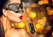 stock photo of golden  - Sexy model woman with glass of champagne wearing venetian masquerade carnival mask at party - JPG