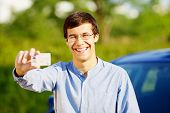 Smiling young man in glasses showing his driving license outdoor in sunny summer day